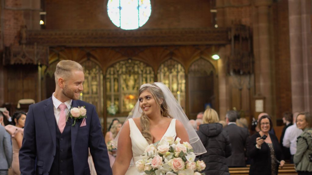 a still from the wedding video of a bride and groom walking down the aisle now married at oxton st saviours