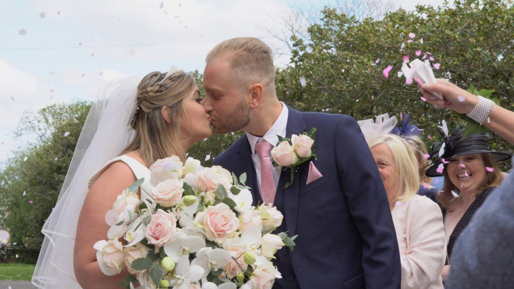 a still from the wedding video of the pink cofetti shot outside church the bride holds an oversized blush pink and white boquet