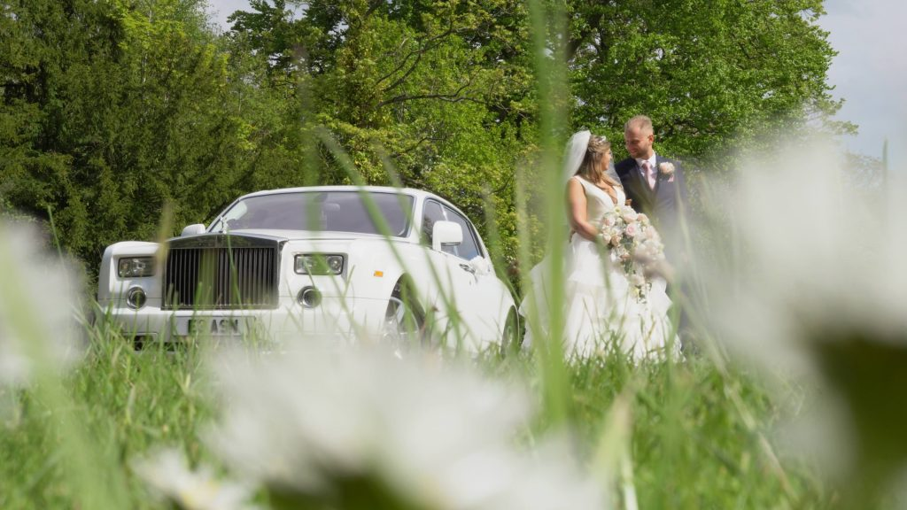 a still from the wedding videographer of the white rolls royce phantom wedding car next to the bride and groom in the gardens at Thornton Manor