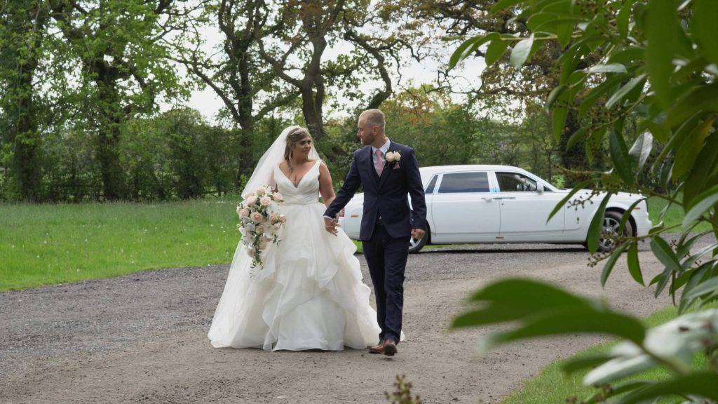 a bride wearing a princess wedding dress and groom in navy walk away from their white rolls royce wedding car at thornton manor