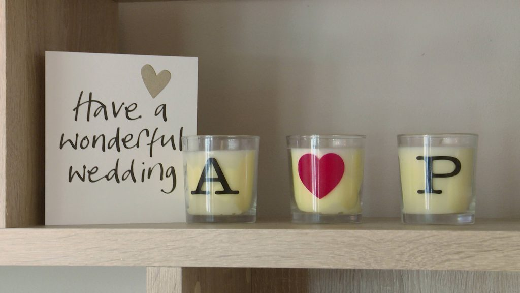 3 candles sit on a shelf next to a wedding card with the bride and grooms initials on