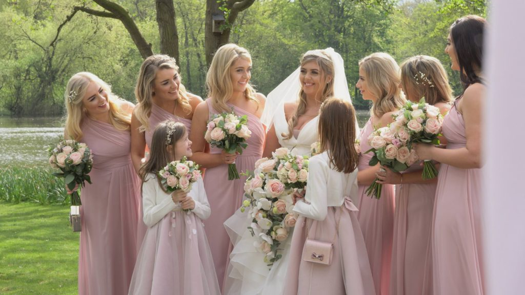 a still from the wedding videographer of the bride and her bridesmaids with blush pink floor length dresses and bouquets