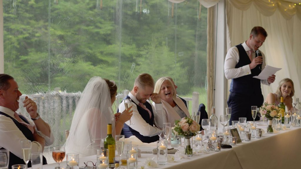 a still from the wedding video of the groom looking embarrassed during the best mans speech at lakeside thornton manor