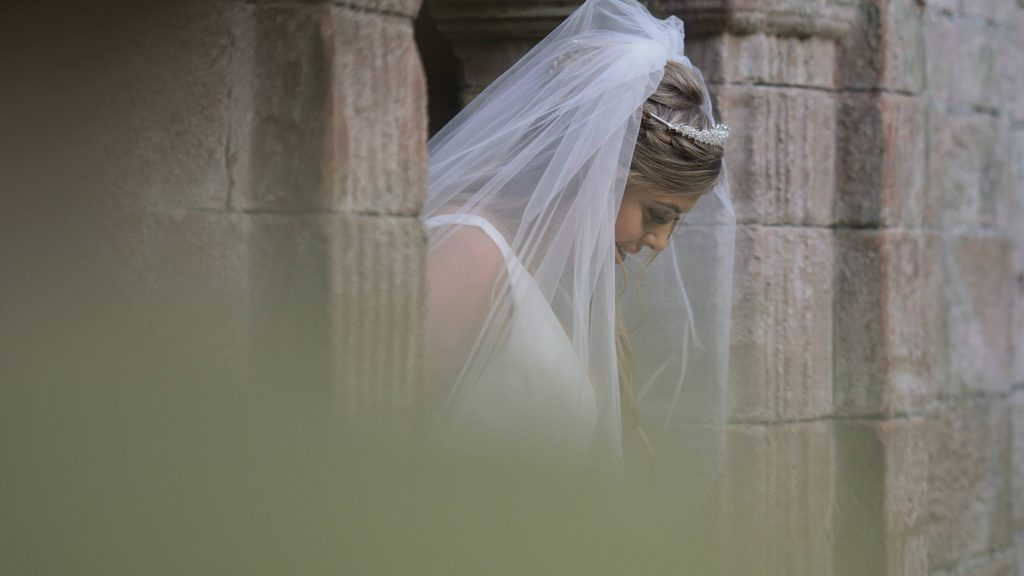 a close up shot of a bride looking down and her wedding veil around her shoulders posing for photos at thornton manor
