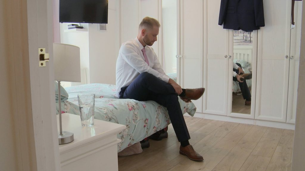 a still from the wedding video of a groom sitting on a bed at his home in Prenton tying his brown leather wedding shoes