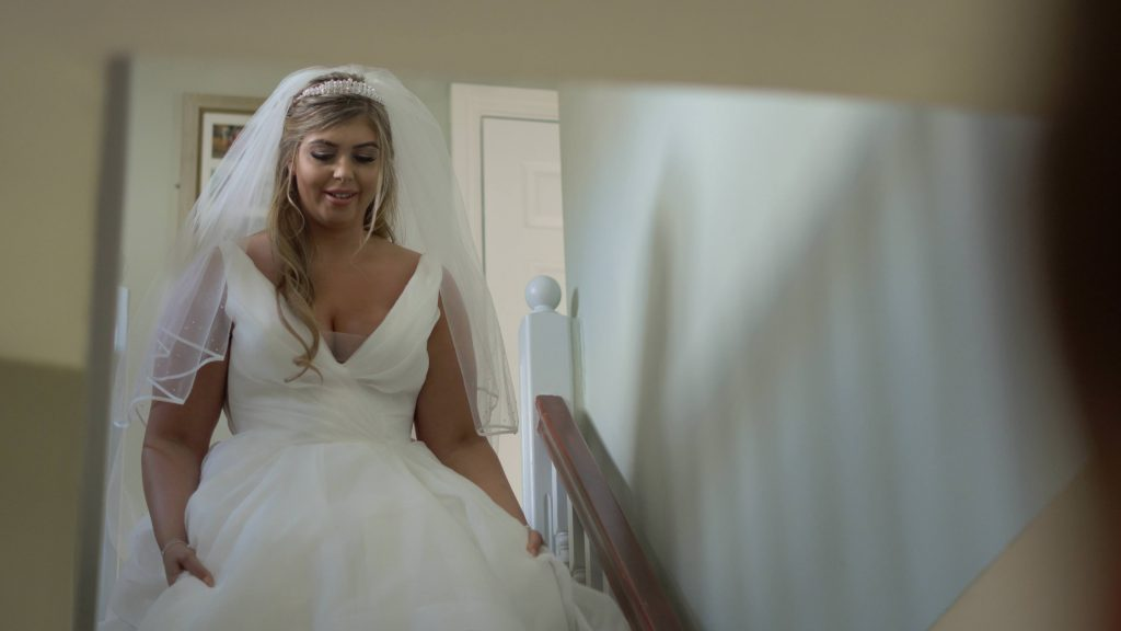 the bride smiles nervously as she walks down the stairs at her parents home in Oxton before she gets married