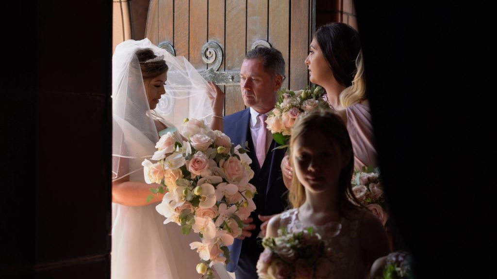 a beautiful still from the wedding videographer of the bride having her veil put in place by her dad moments before she walks down the aisle at Oxton St Saviours