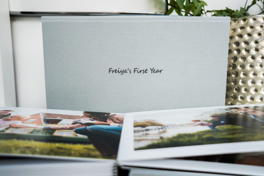 a family album lays open on a table at the home of a family photographer in lancashire with the personalised cover reading Freiyas first year