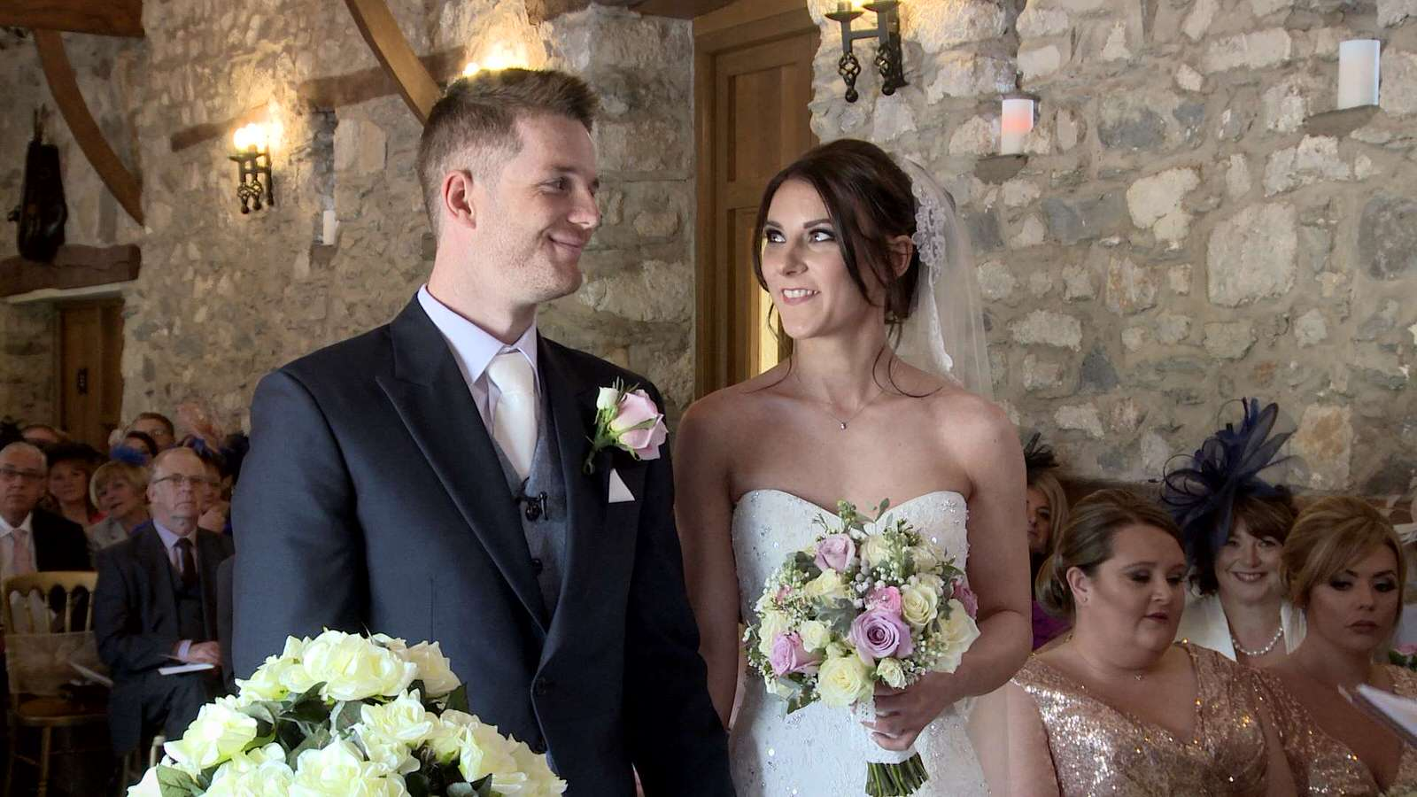 bride and grooms smile during their wedding ceremony at Plas Isaf barn in north wales