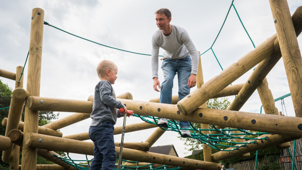 a dad and his son play on the climbing frame at a local park in Wetherby
