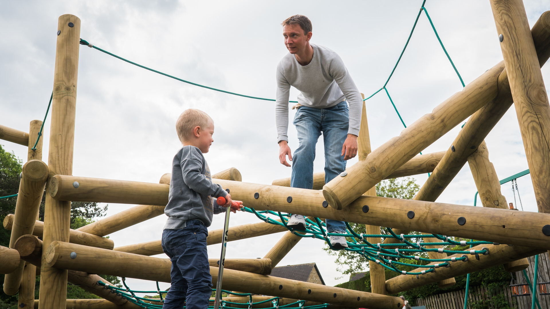 a dad and boy play on climbing frame at a local park in Wetherby