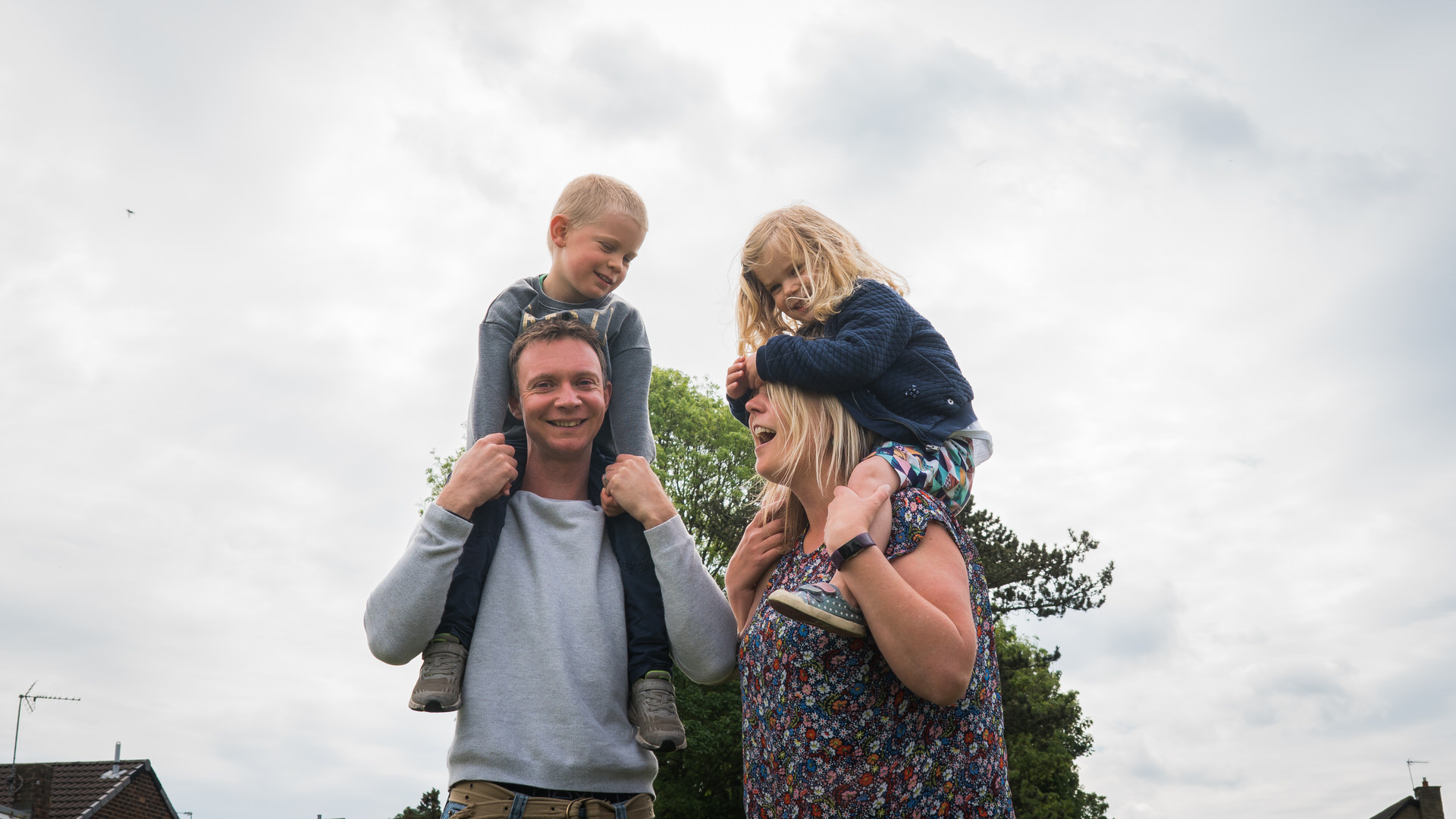 an alternative family portrait of a family being silly with the kids on shoulders at the park