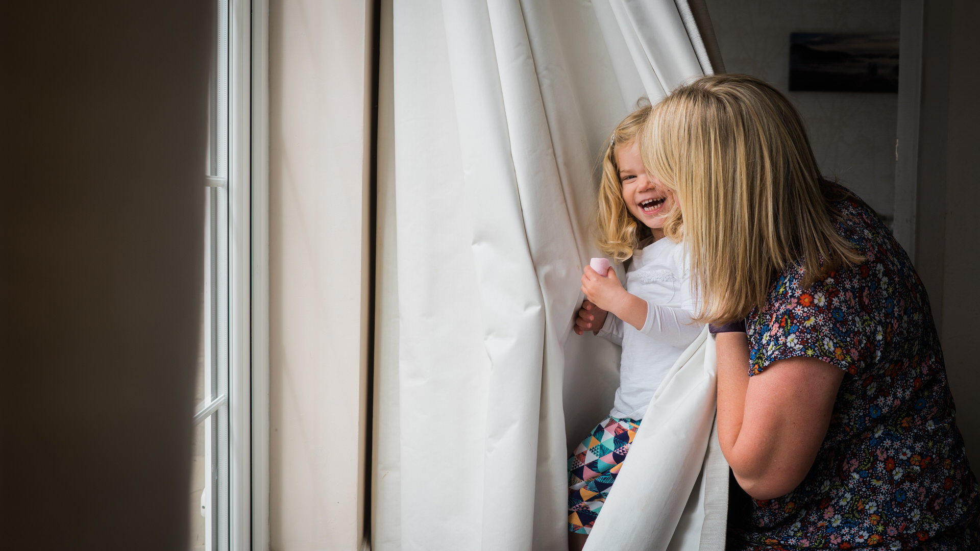 a natural photograph of girl playing peekaboo with her mum and photographer