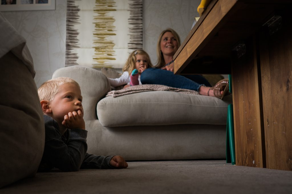 a real life family shot of a mum sitting with her daughter and son watching TV at home