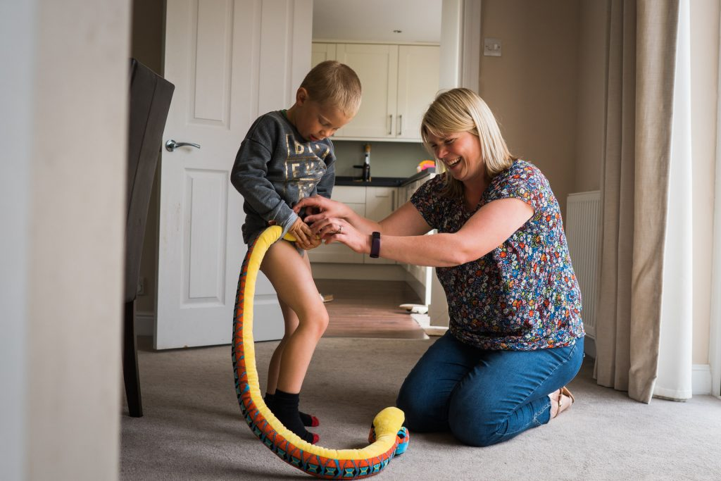 a mum laughs as she helps her son sort out his snake in to a dinosaur tale during a family shoot