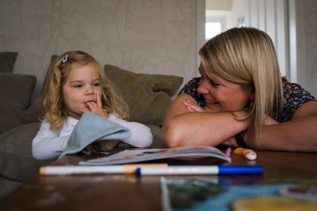 a mum leans on her arms and smiles at her daughter during their home family photo shoot in Wetherby