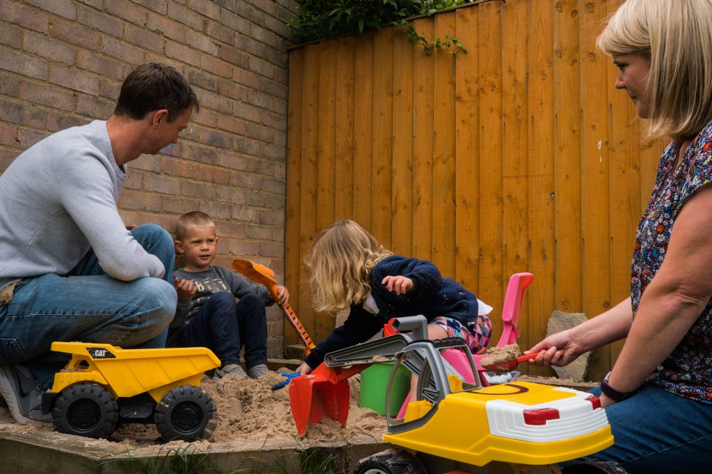 a dad plays in the garden sand pit during a family photo shoot in Wetherby