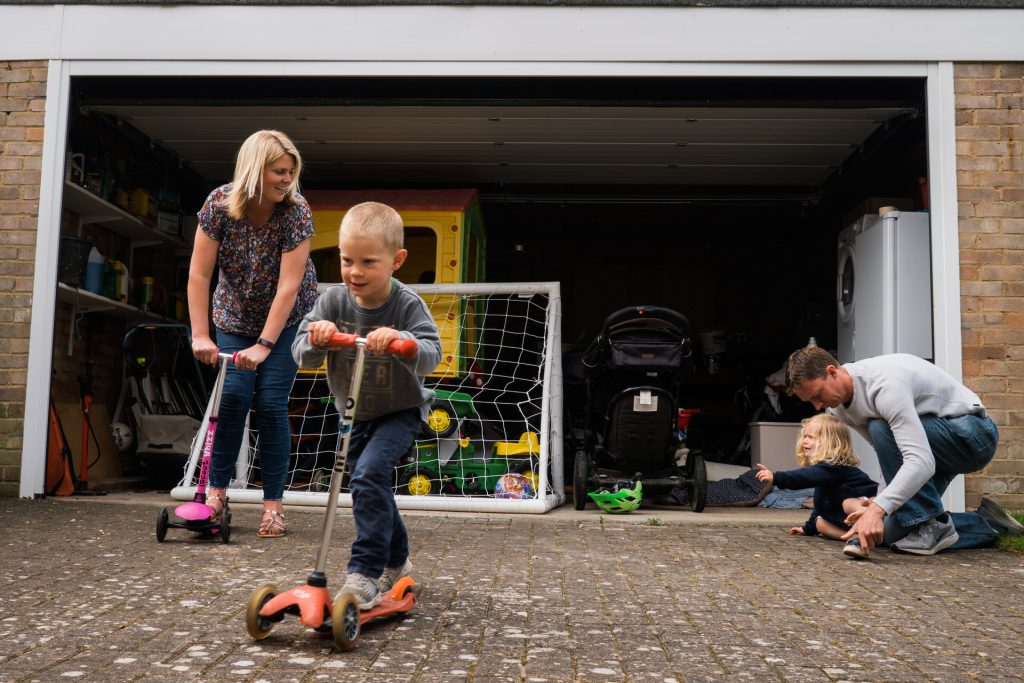 a documentary style photograph of a family racing on scooters outside their home and an upset daughter