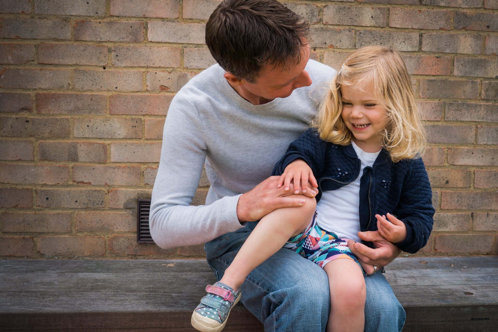a little girl sits on her dads knee giggling during a relaxed family photo shoot by love gets sweeter