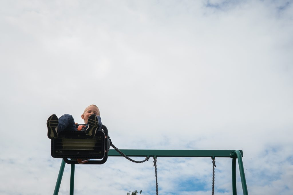 a photograph of a young boy swinging high up on the park swings during an outdoor family session photo shoot