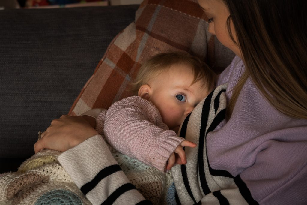a little girl looks up at the camera whilst breastfeeding during a family photo shoot at home in Lancashire