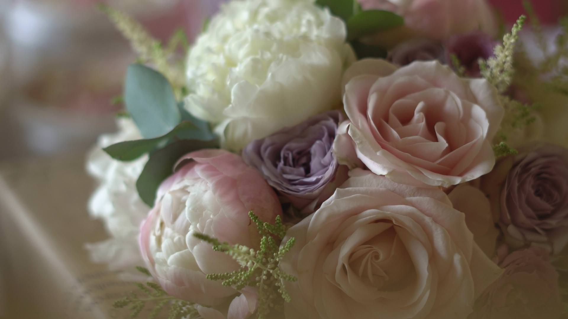 a close up of a bridal bouquet of peonies in pick and white
