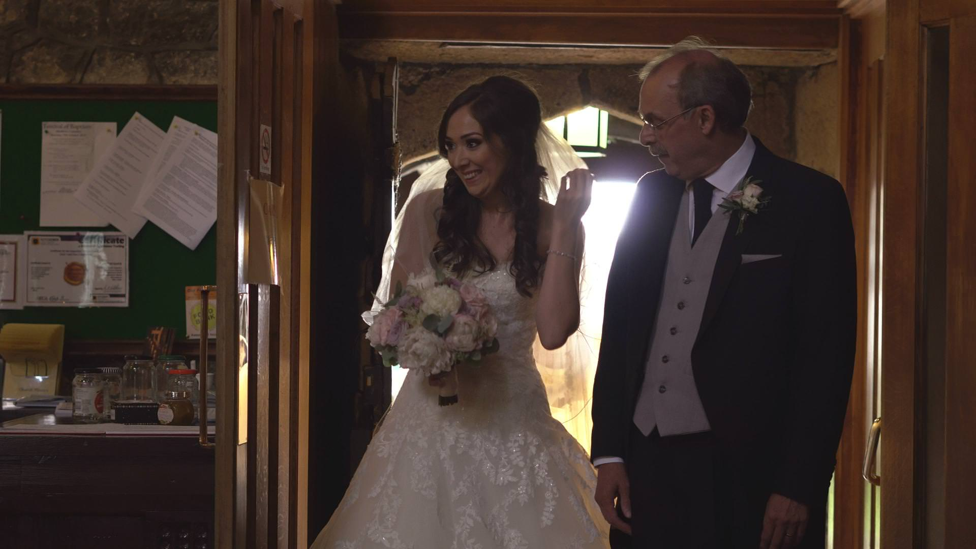 a bride smiles before she walks down the aisle at St Bartholomews and St John's Church Great Harwood