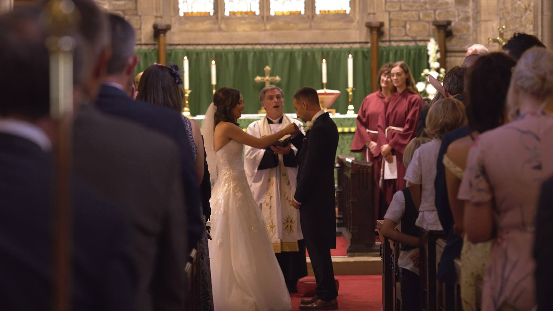 the groom coughs on to the brides hand during vows at St Bartholomews and St John's Church,