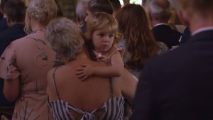 a close up wedding video still of a little girl during the ceremony