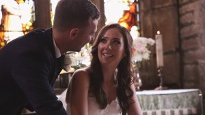 a bride looks up at her groom during the signing of the register