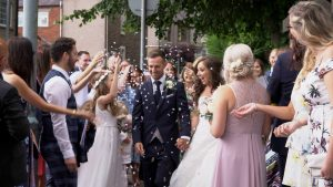 a bride a groom laugh as they get showered in Dollz confetti during a Lancashire wedding