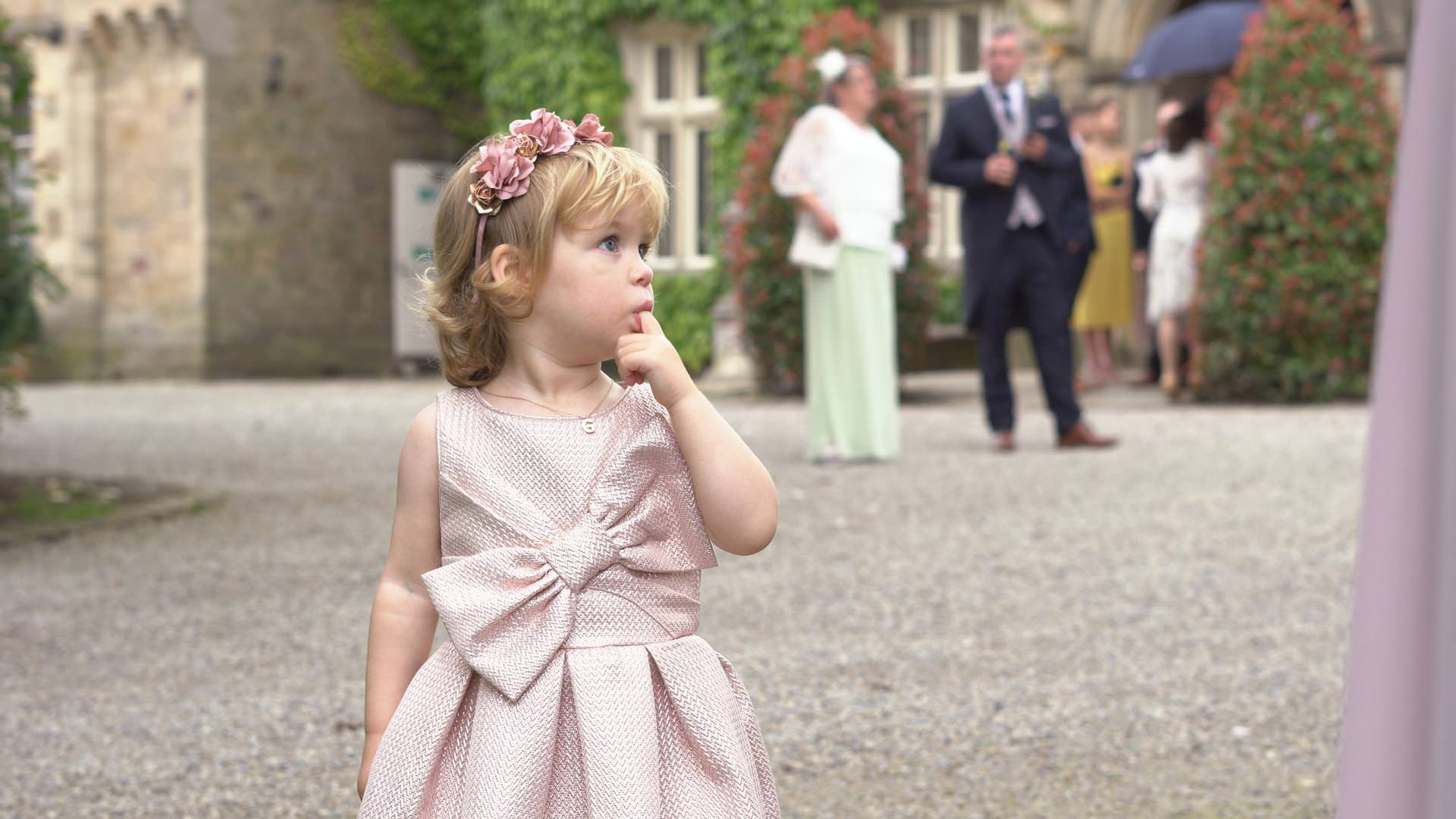 a cute little girl with a flower crown looks on at a wedding at Mitton Hall