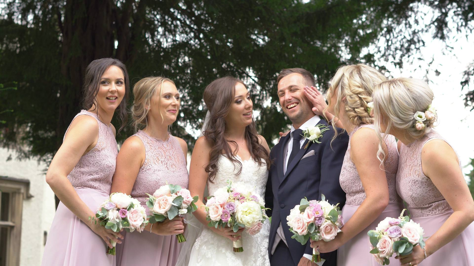 the groom laughs as the bridesmaids fuss over him during wedding photos at Mitton Hall