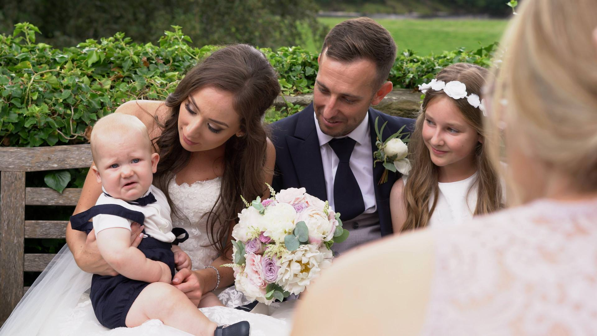 a baby boy doesn't look impressed being made to pose for wedding photos at Mitton Hall in Lancashire