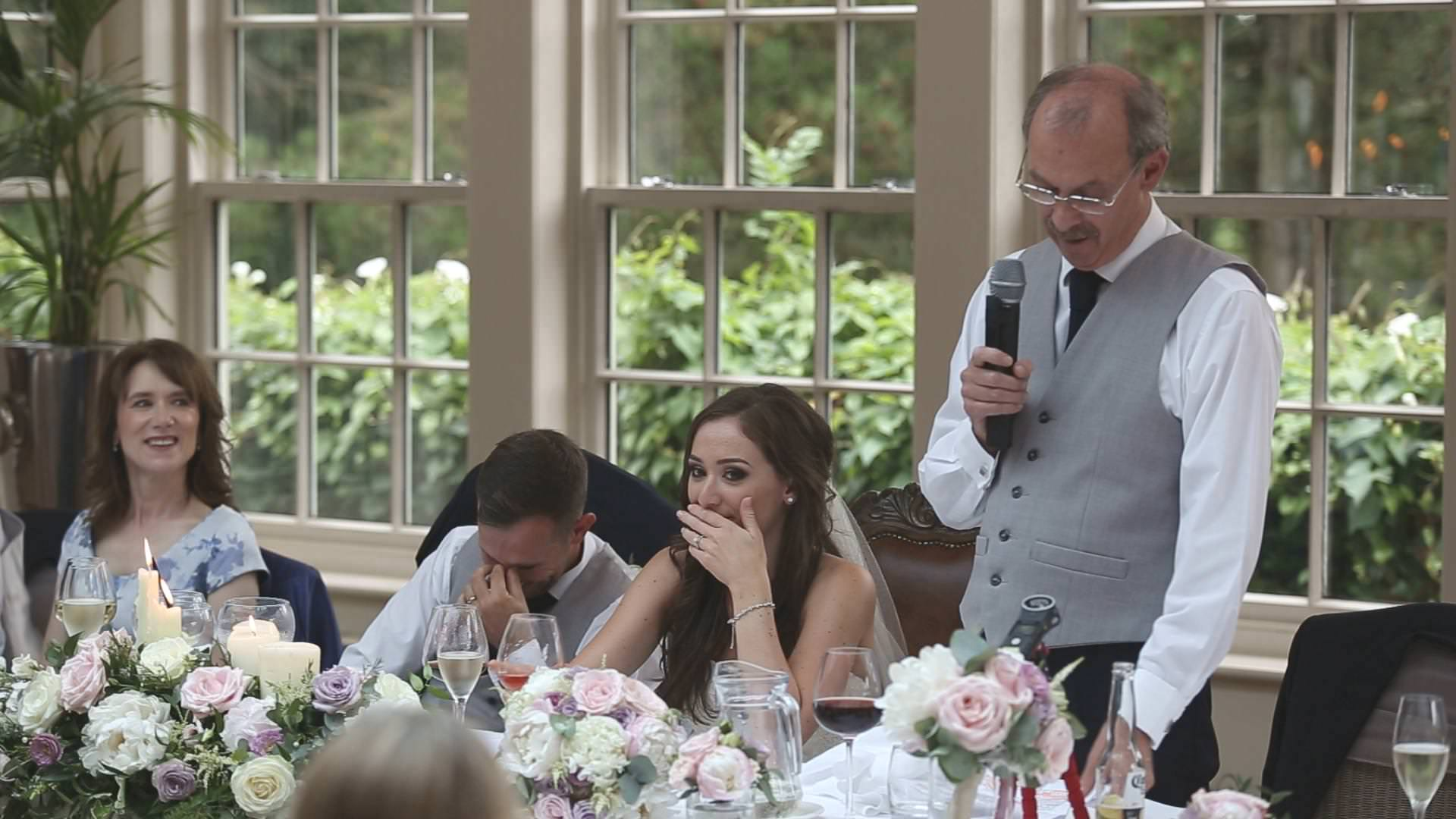 a bride and groom hide their faces during a father of the bride speech at mitton hall
