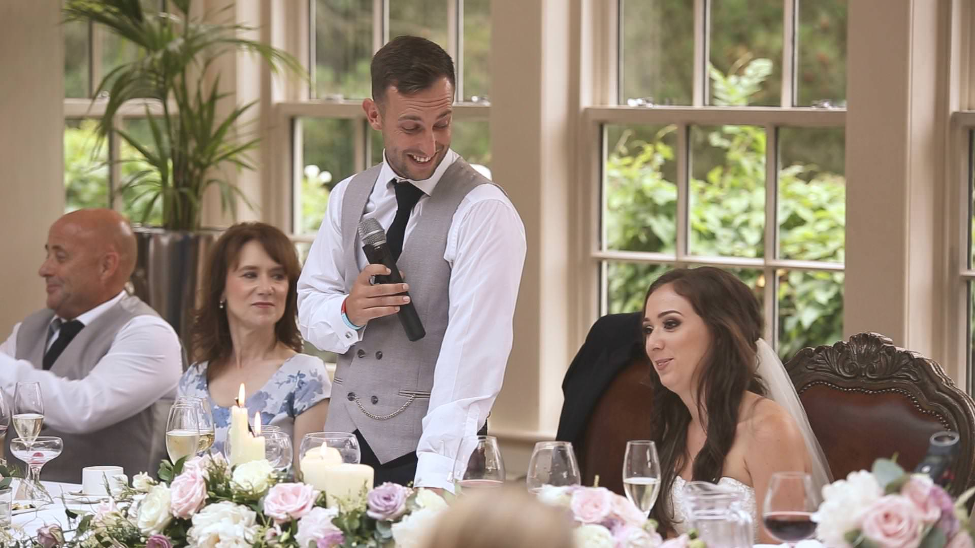 a groom smiles at his bride during his speech at Mitton Hall