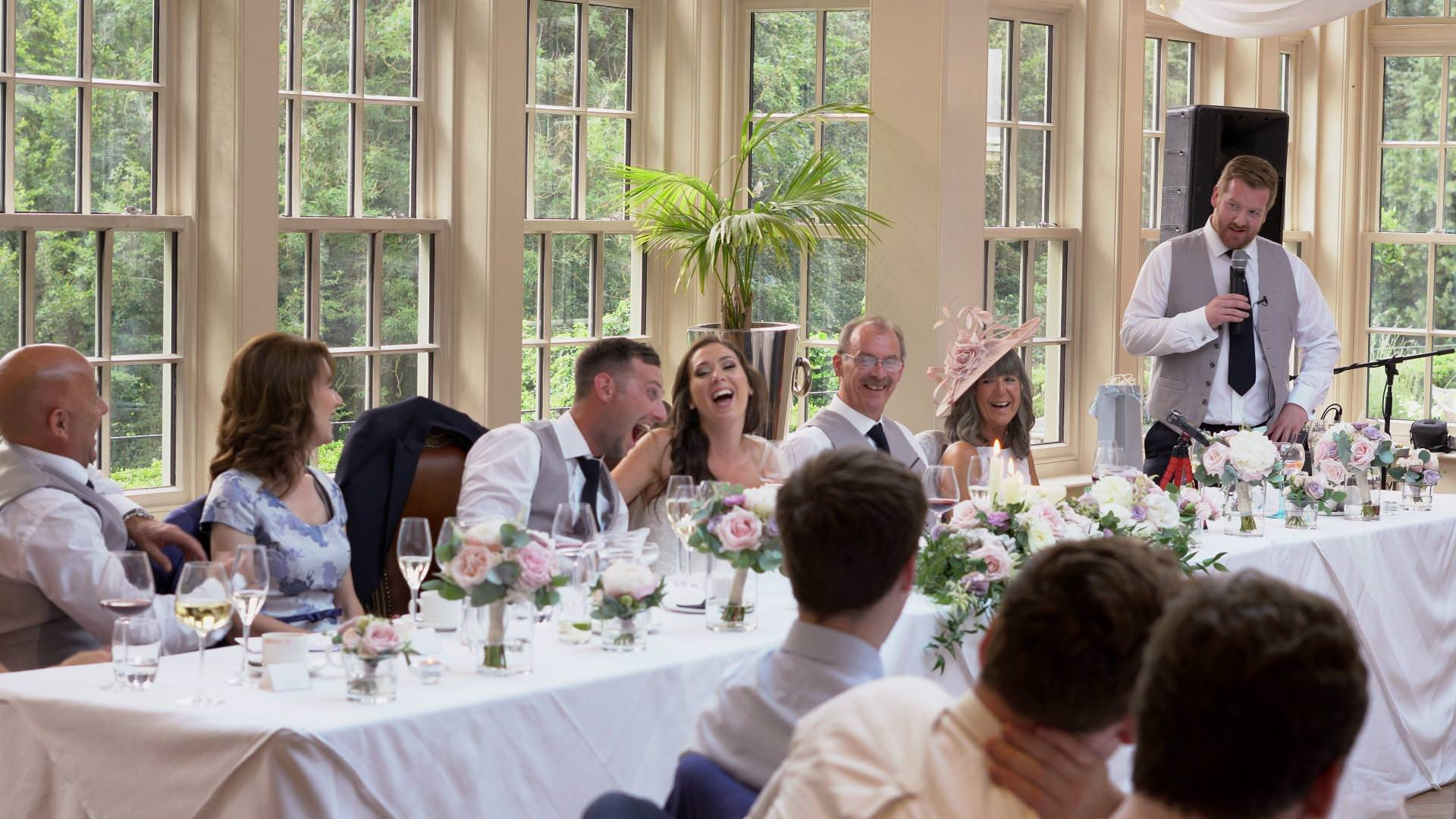 a wedding video still of the whole top table laughing during a best man speech at Mitton hall