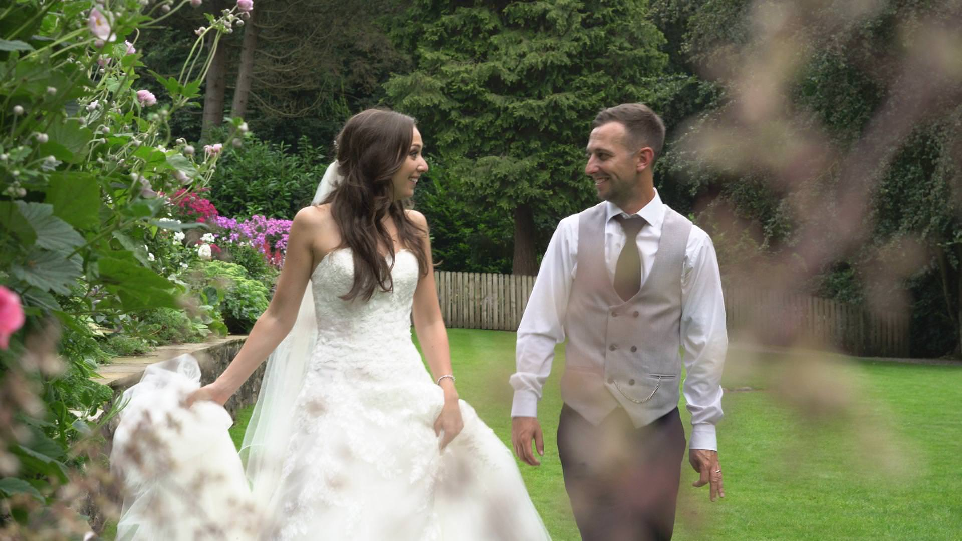 a bride and groom go for a relaxed walk at mitton hall for photos and video