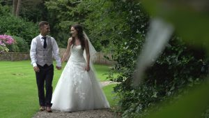 a bride and groom hold hands and walk around mitton hall for photographs