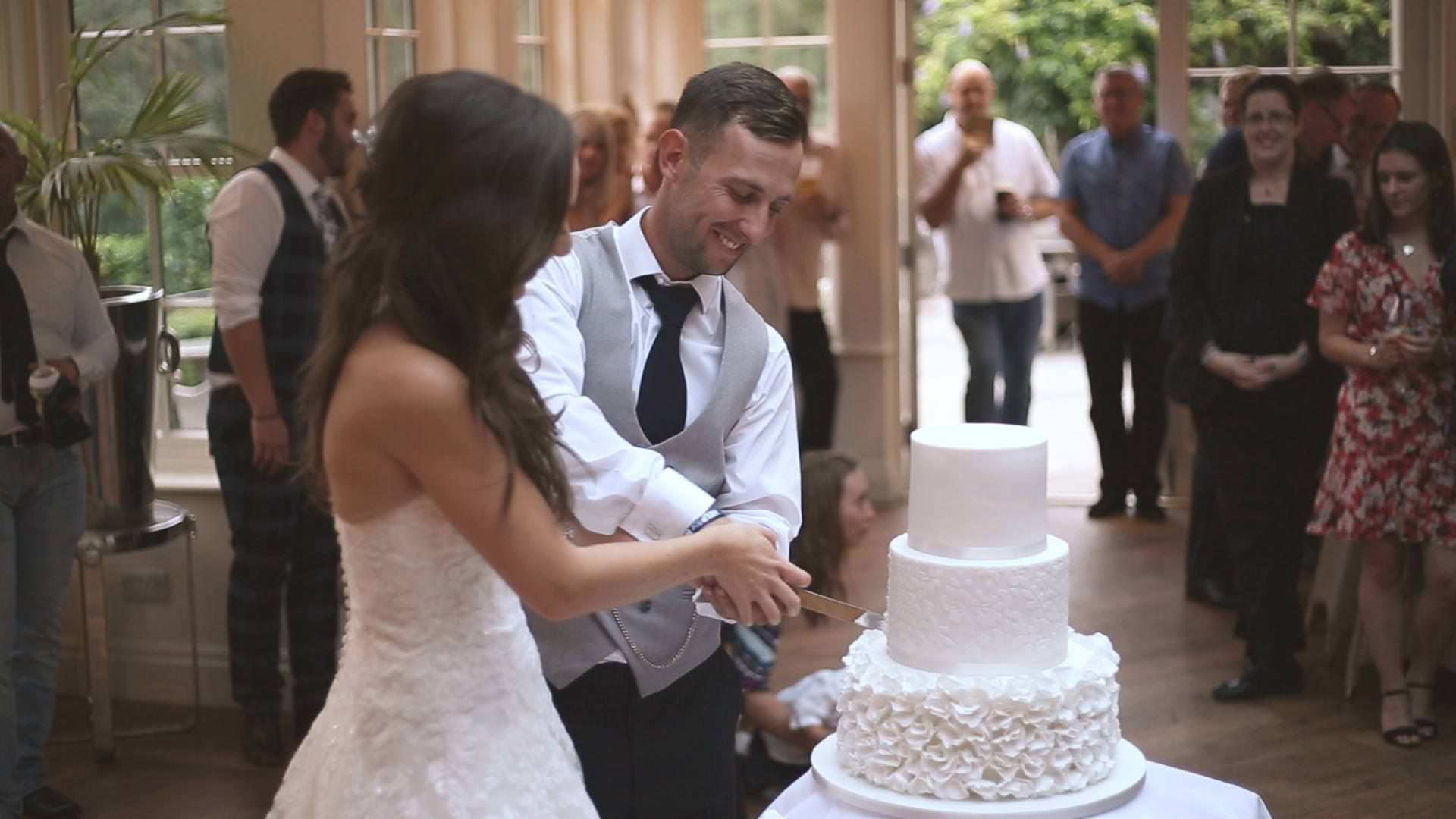 a bride and groom cut their white wedding cake at mitton hall in Lancashire