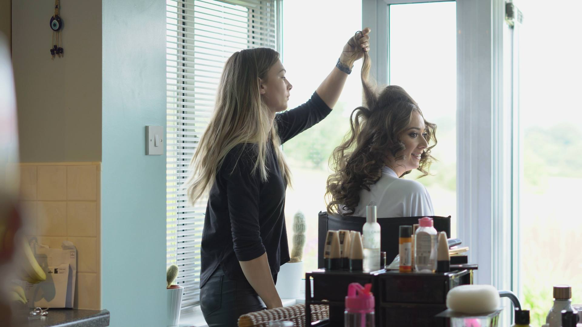 a bride gets her hair done at home before her wedding