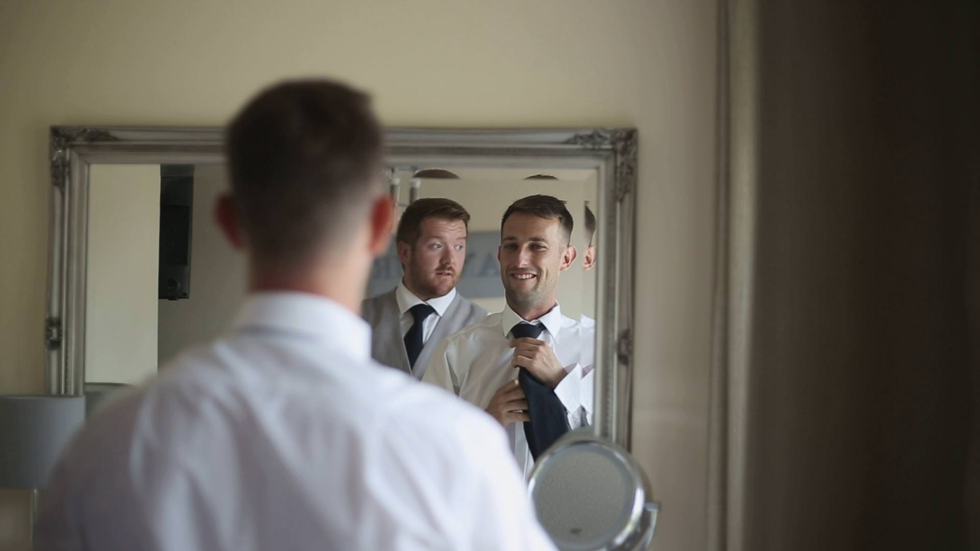 a wedding video still of a groom and best man doing their ties in the mirror in Lancashire