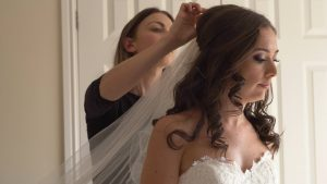a make up artist add the brides veil before she heads to church