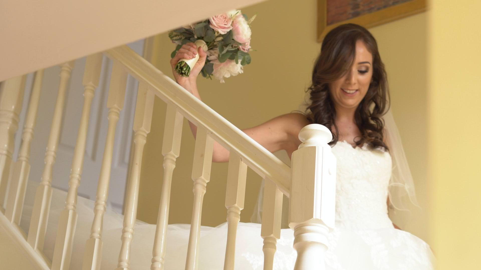 a bride walks down the stairs holding her bridal bouquet in Lancashire