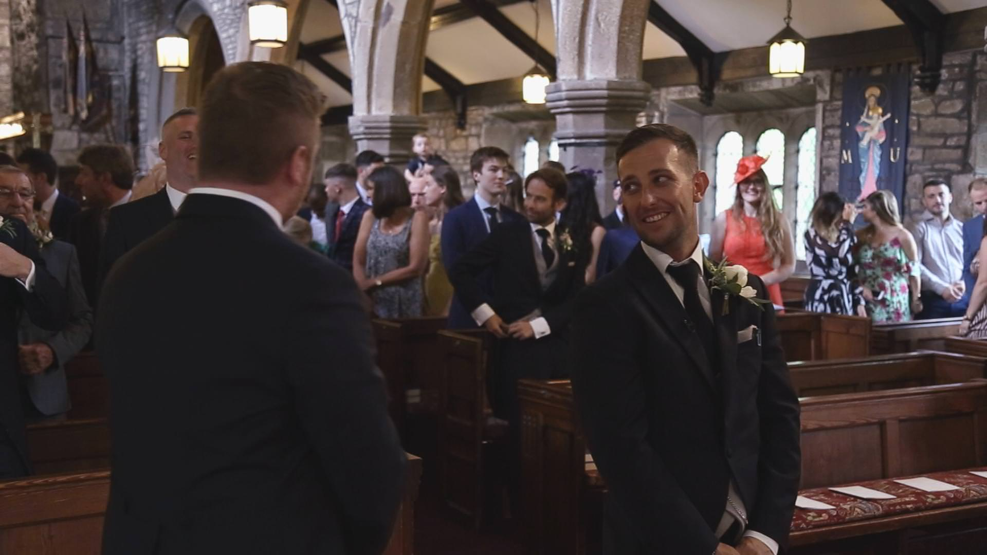 a groom smiles at his best man before a wedding ceremony at St Bartholomews and St John's Church in Great Harwood