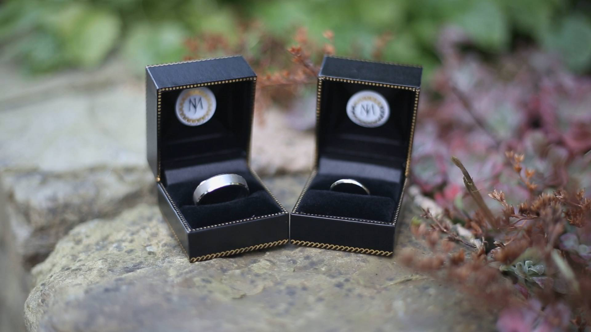 platinum wedding rings sit in their boxes before a wedding in lancashire