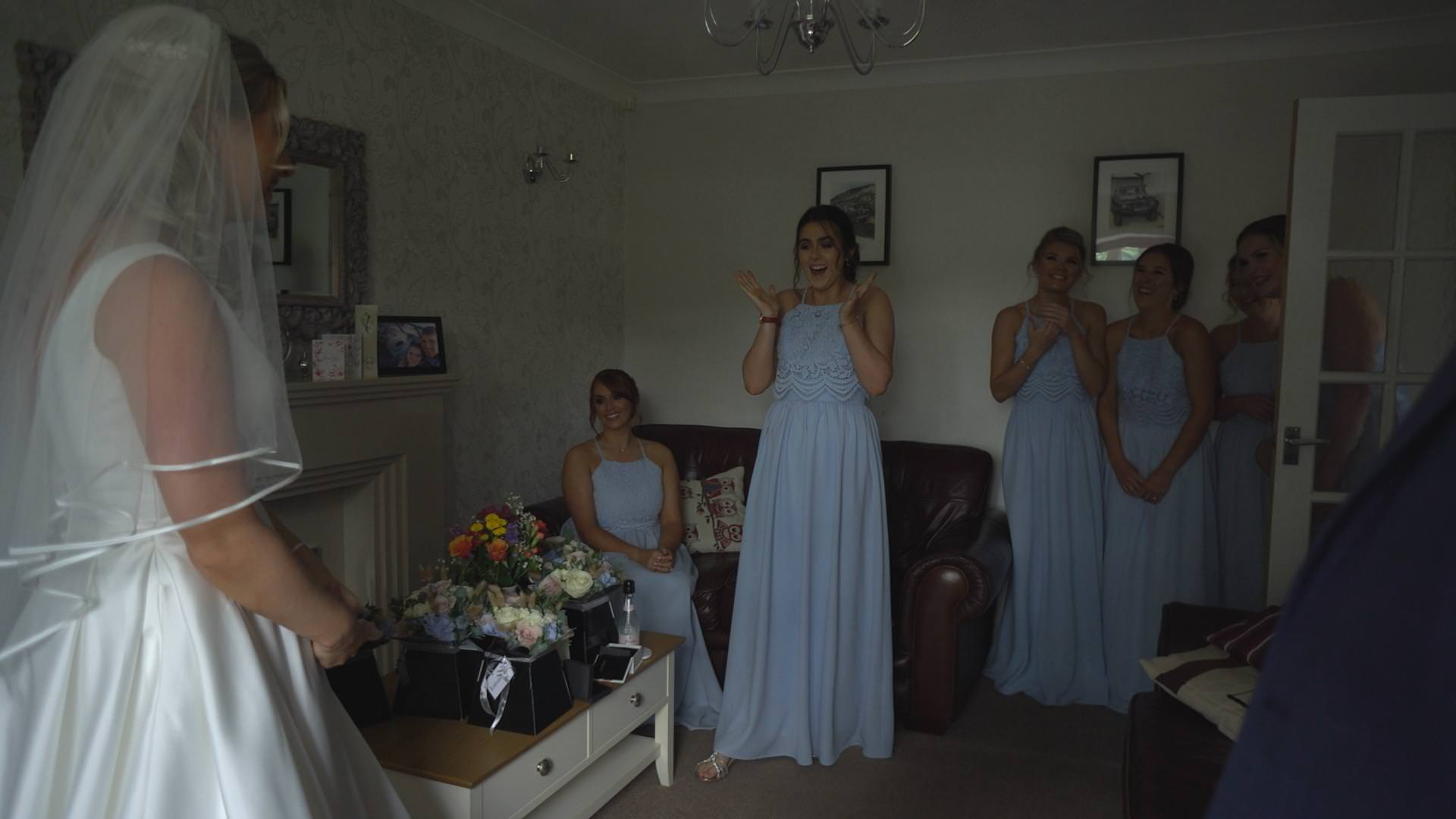 bridesmaids wearing baby blue dresses react to seeing the bride for the first time