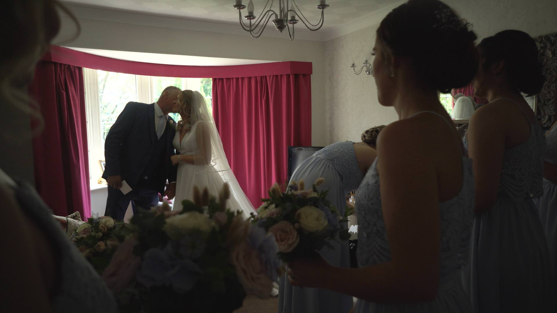 a video still of dad kissing the bride before they leave for church