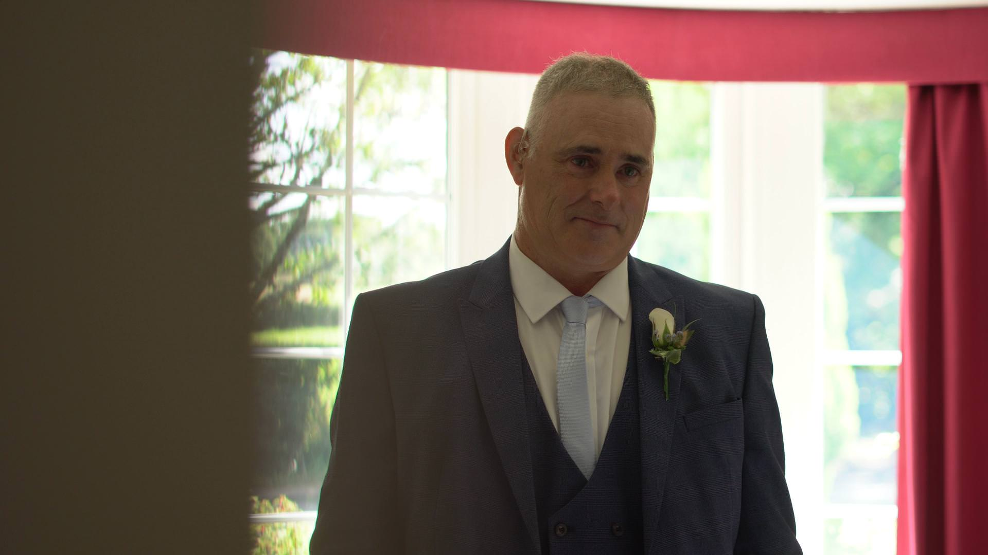 a video still of an emotional looking father of the bride