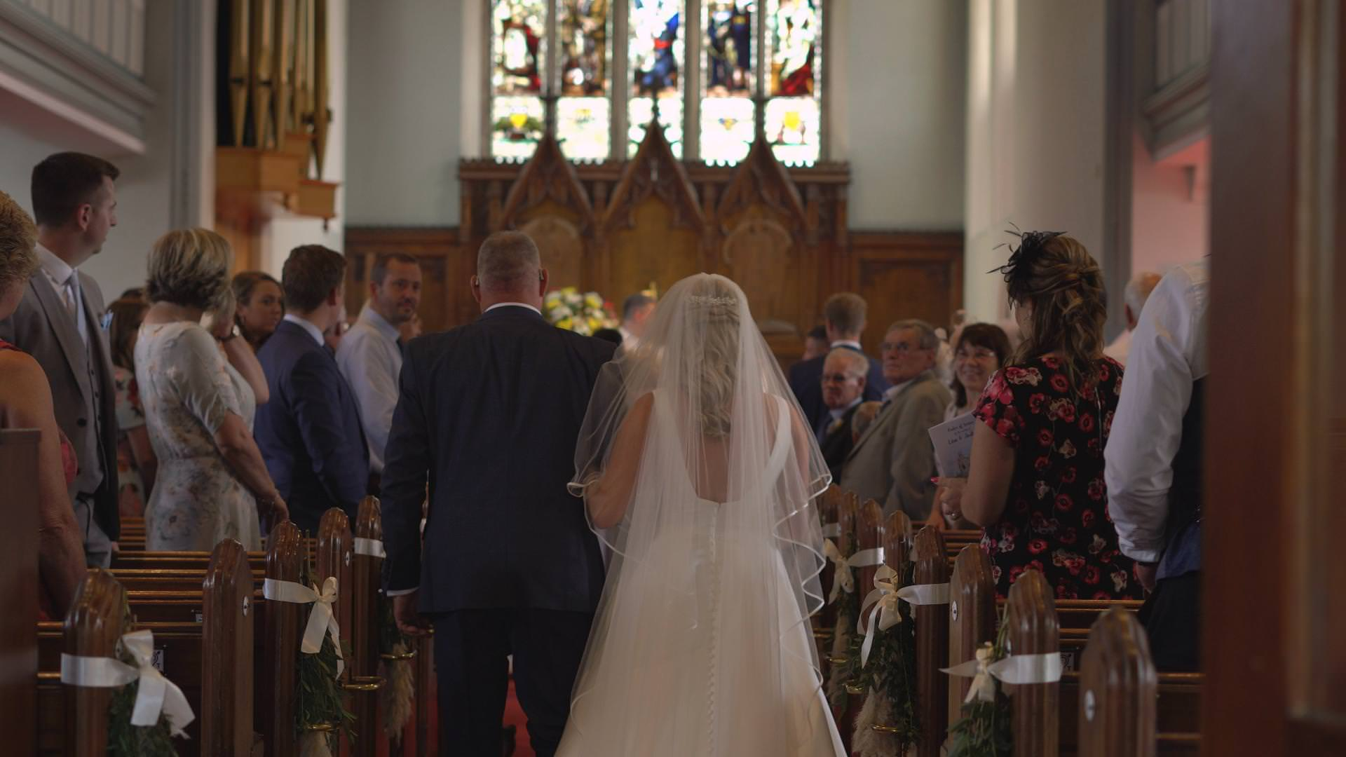 a video still of a bride walking down the aisle at St Johns church in Burscough